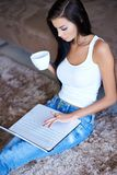 Woman relaxing with coffee and her laptop Royalty Free Stock Photo