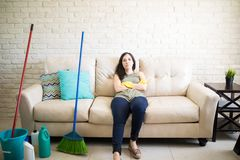 Woman relaxing after completing house cleanup Stock Images