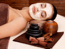 Woman relaxing with cosmetic mask on face Stock Photos