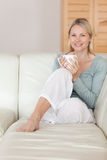 Woman relaxing on the couch with a cup of coffee Royalty Free Stock Image