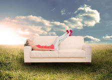 Woman relaxing on couch in field. Woman relaxing on  the couch in sunny field in the countryside Stock Images
