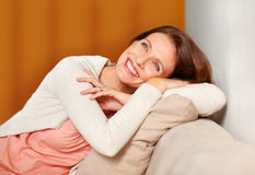 Woman relaxing on couch having a happy thought Royalty Free Stock Image