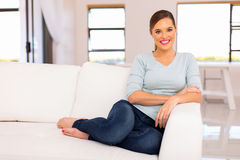 Woman relaxing couch. Smiling woman relaxing on a couch at home Royalty Free Stock Images