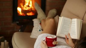 Woman relaxing on couch with warm drink and good book. Holding hot chocolate mug by the fireplace and reading, camera dolly stock video footage