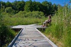 Woman relaxing in countryside. Young woman relaxing in countryside on bench on wooden boardwalk Royalty Free Stock Image