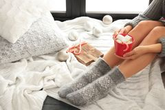 Woman relaxing with cup of hot winter drink on knitted plaid. Space for text royalty free stock image