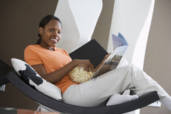 Woman relaxing in curved chair at home, reading magazine, feet up, smiling, side view, portrait (tilt) Stock Images