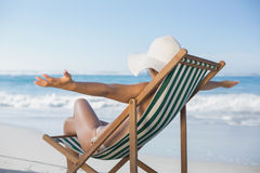 Woman relaxing in deck chair with arms outstretched Royalty Free Stock Photos