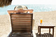 Woman relaxing on deck chair at beach resort Royalty Free Stock Images