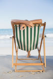 Woman relaxing in deck chair on the beach Stock Photo