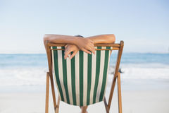 Woman relaxing in deck chair on the beach Royalty Free Stock Photo