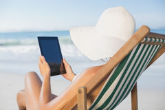 Woman relaxing in deck chair on the beach using tablet Stock Photos