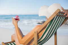 Woman relaxing in deck chair with cocktail Stock Image