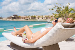 Woman relaxing in deck chair by the pool Stock Photos