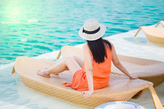 Woman  relaxing in deck chair by the pool Stock Image