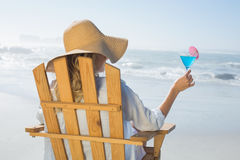 Woman relaxing in deck chair by the sea holding cocktail Royalty Free Stock Photography