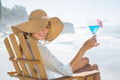 Woman relaxing in deck chair by the sea holding cocktail Stock Photos