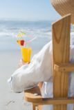 Woman relaxing in deck chair by the sea holding cocktail Stock Images