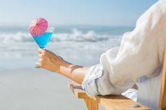 Woman relaxing in deck chair by the sea holding cocktail Royalty Free Stock Image