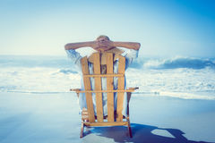 Woman relaxing in deck chair by the sea Royalty Free Stock Image