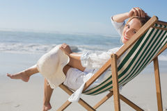 Woman relaxing in deck chair by the sea Stock Image