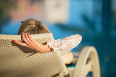 Woman relaxing in deck chair by the swimming pool Royalty Free Stock Photography