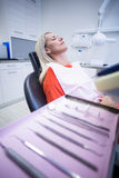 Woman relaxing on dentist chair with dental tools on foreground Royalty Free Stock Image