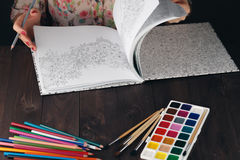 Woman relaxing while do painting adult coloring book Stock Image