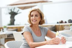 Woman relaxing with a drink of water at outdoors restaurant Stock Image