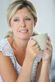 Woman relaxing drinking a cup of tea Stock Photo
