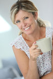 Woman relaxing drinking hot tea Stock Images