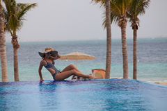 Woman relaxing at the edge of an infinity pool Stock Image