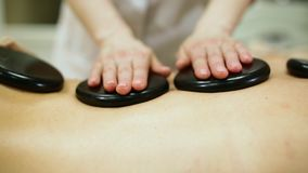 Woman relaxing enjoying hot stone massage at the spa stock video footage