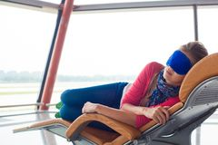 Woman relaxing in eye sleep mask at airport stock image