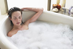 Woman Relaxing With Eyes Closed In Bathtub royalty free stock photos