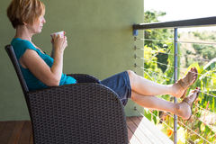 Woman relaxing with feet up. Woman relaxing drinking tea/coffee on balcony enjoying the view Royalty Free Stock Photos