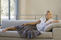 Woman relaxing with feet up on sofa at home, smiling, side view, portrait stock photos