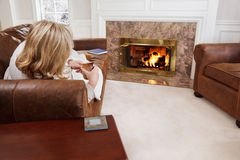Woman relaxing by fire Stock Image
