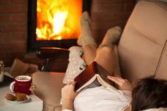 Woman relaxing by the fire with a good book some cookies and hot Stock Image