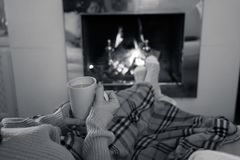 Woman relaxing by the fireplace warming up feet in woolen with a cup of hot drink socks and blanket. Close up image of woman sitting under the blanket by cozy stock photos