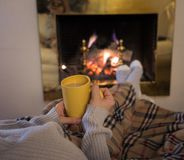 Woman relaxing by the fireplace warming up feet in woolen with a cup of hot drink socks and blanket. Close up image of woman sitting under the blanket by cozy royalty free stock image