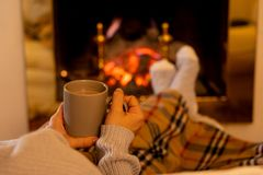 Woman relaxing by the fireplace warming up feet in woolen with a cup of hot drink socks and blanket. Close up image of woman sitting under the blanket by cozy royalty free stock images