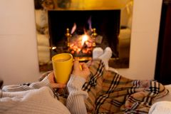 Woman relaxing by the fireplace warming up feet in woolen with a cup of hot drink socks and blanket. Close up image of woman sitting under the blanket by cozy royalty free stock photography
