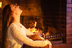 Woman relaxing at fireplace. Winter home. Stock Image