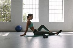 Woman relaxing at fitness club after training session. Side view of fitness female sitting on exercise mat at the fitness club after training session. Taking Stock Photography