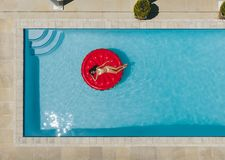 Woman relaxing on floating mattress in pool Royalty Free Stock Image