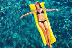 Woman Relaxing Floating on Raft in Pool Stock Photos