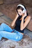 Woman relaxing on the floor listening to music Stock Photos