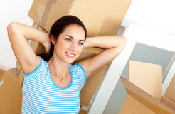 Woman relaxing on the floor after unpacking boxes Stock Photos