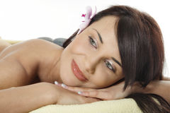 Woman relaxing with flower and hot stones Stock Image